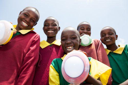 School children from Kembu primary school holding solar lights, Longisa, Bomet county, Kenya