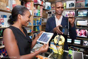 Samson Mtamanga, Sunny money agent showing light to customer, Kawa General shop, Kericho, Kenya