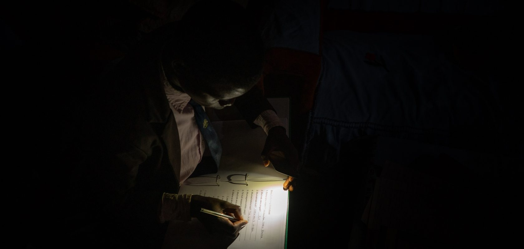 William Banda using a cell phone to light his notes