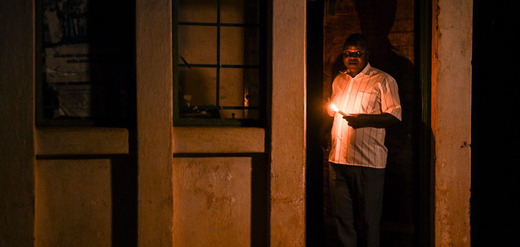 TA Kasakula holding a candle in a doorway.